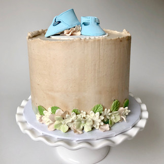 Baby shower cake with baby boots on top