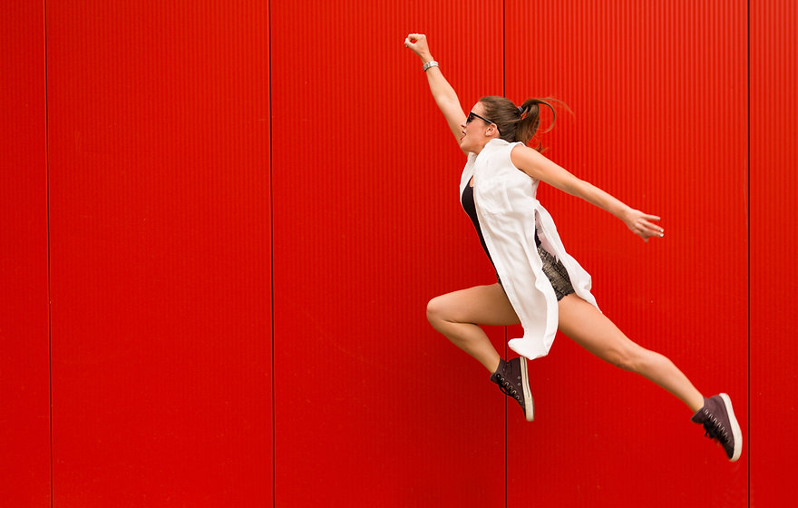 Stylish woman dancing and jumping on a street against a red wall.jpg
