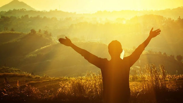 Man giving praise and lifting hands towards the sun.