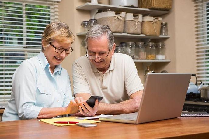 Glada seniorer vid datorn