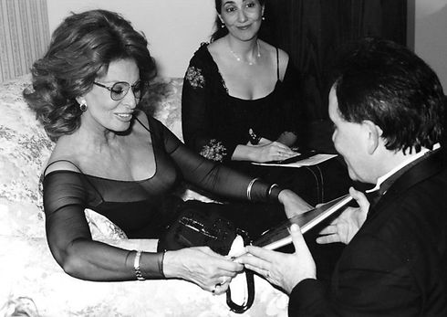 sophia loren being gifted book by peter mercanti while other woman watches on