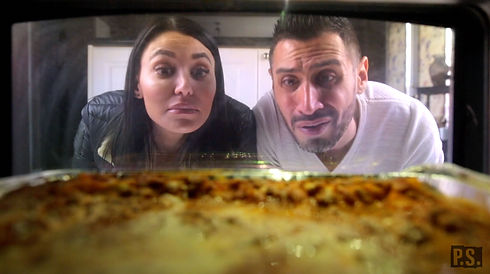 brother and sister watch lasagna cooking through window in oven