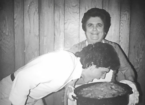man taking a bite of a fresh baked lasagna his mother is holding