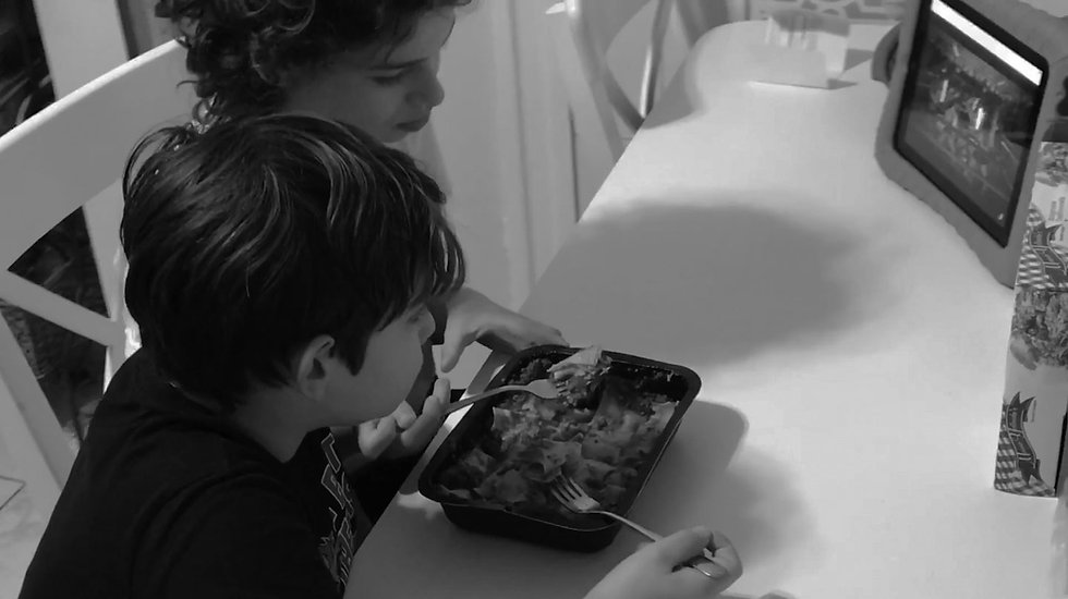 two young children eating microwaved lasagna and watching show on tablet