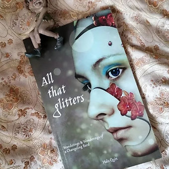 Book - All That Glitters - with cheeky fairy statue sat on top.