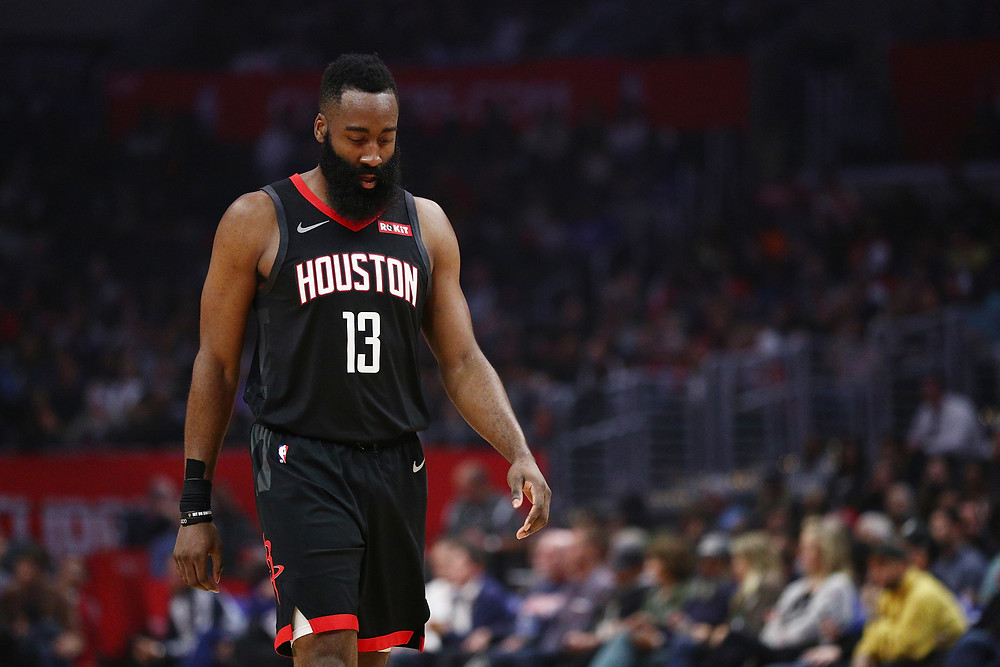 Houston Rockets shooting guard James Harden looks down at the floor of Toyota Center during an NBA basketball game.