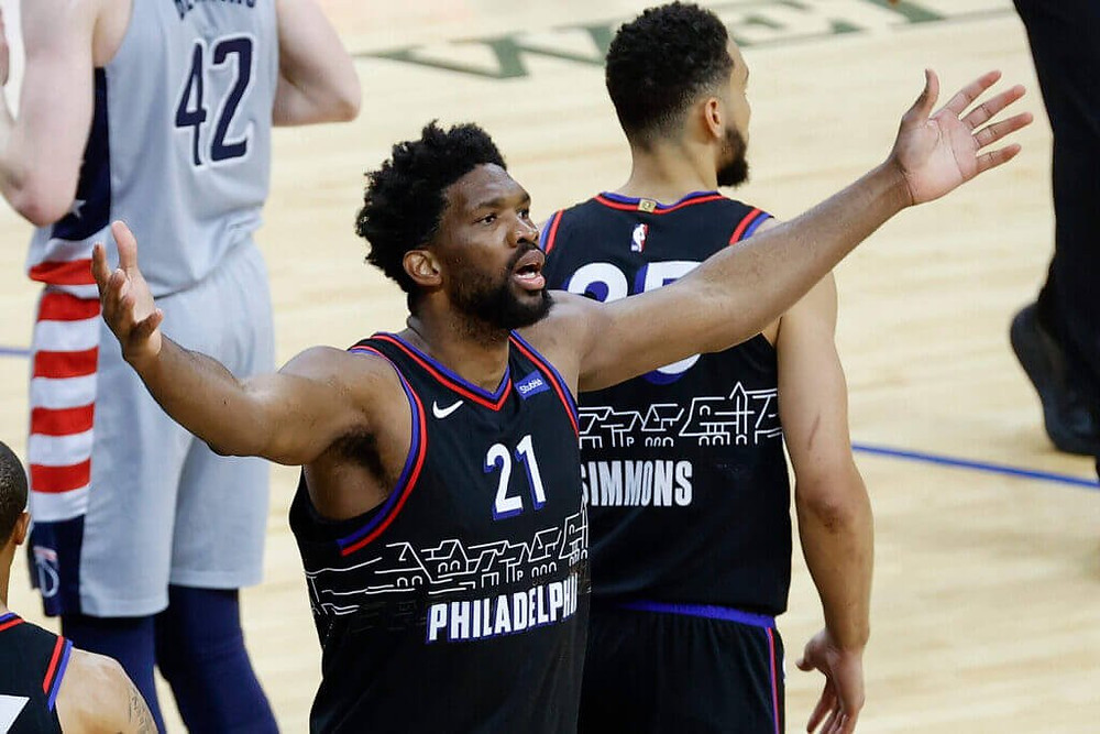Philadelphia 76ers center Joel Embiid cheers on fans during an NBA playoff basketball game against the Washington Wizards.