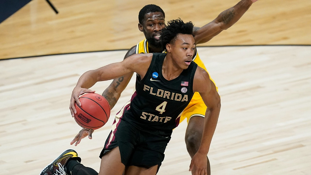 Florida State Seminoles forward Scottie Barnes dribbles the basketball past a defender during an NCAA basketball game against the Michigan Wolverines.