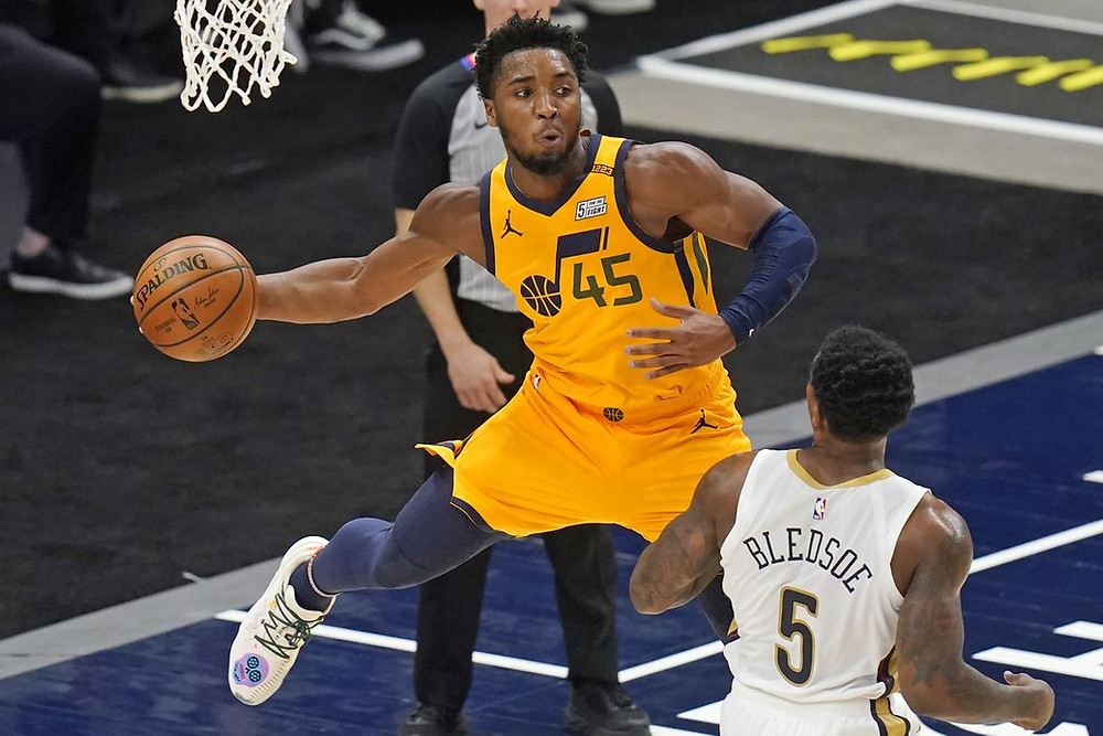 Utah Jazz guard Donovan Mitchell throws a midair pass from under the basket while New Orleans Pelicans guard Eric Bledsoe watches during an NBA basketball game on January 19.