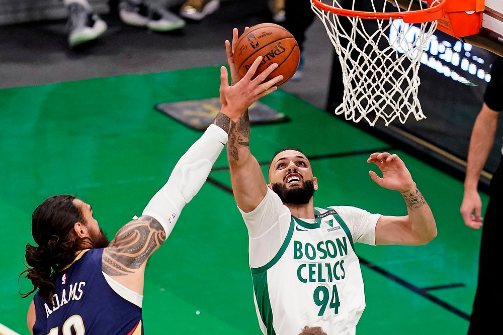 Boston Celtics shooting guard Evan Fournier goes up for a layup against center Steven Adams during an NBA basketball game against the New Orleans Pelicans.