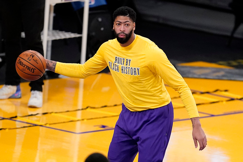 Los Angeles Lakers forward Anthony Davis prepares to pass a basketball to a team trainer during warmups before an NBA basketball game.