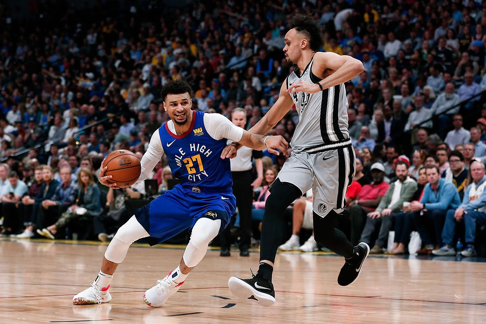 Jamal Murray of the Denver Nuggets drives past Derrick White of the San Antonio Spurs.