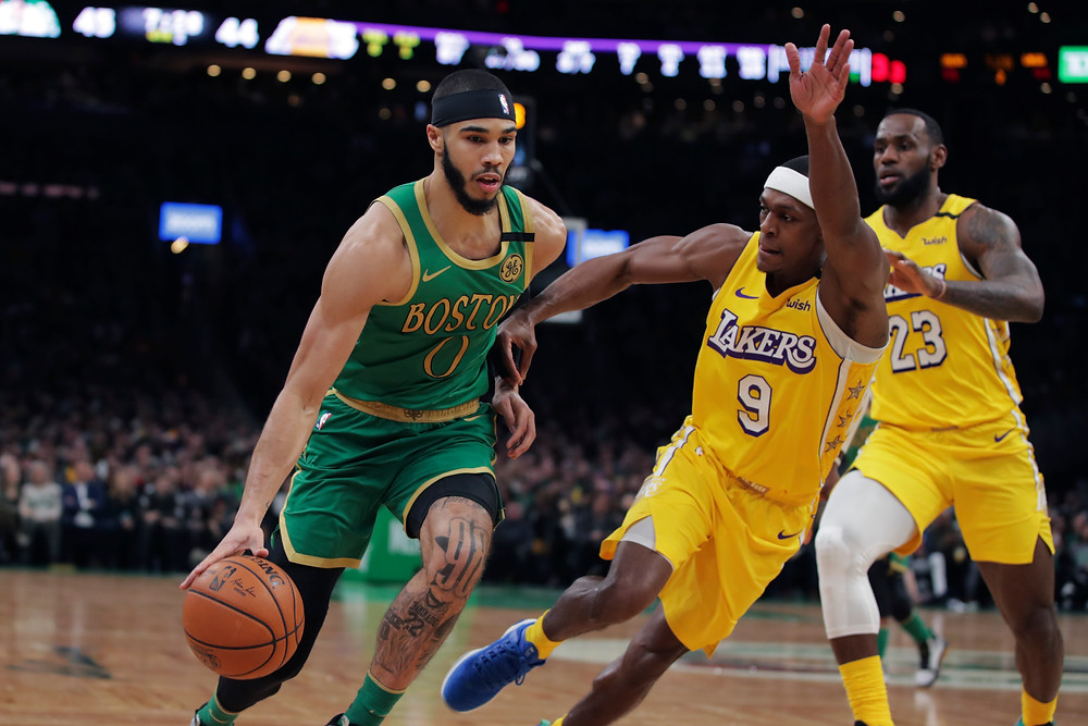 LeBron James of the Los Angeles Lakers watches as teammate Rajon Rondo defends Boston's Jayson Tatum in an NBA game.