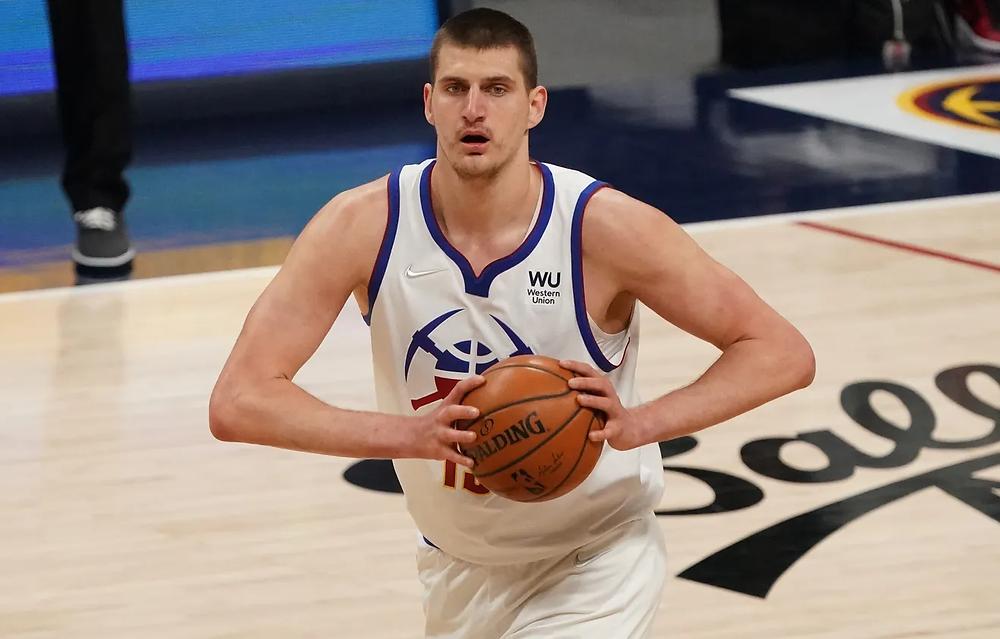 Denver Nuggets center Nikola Jokic prepares to pass to his teammate during an NBA basketball game.