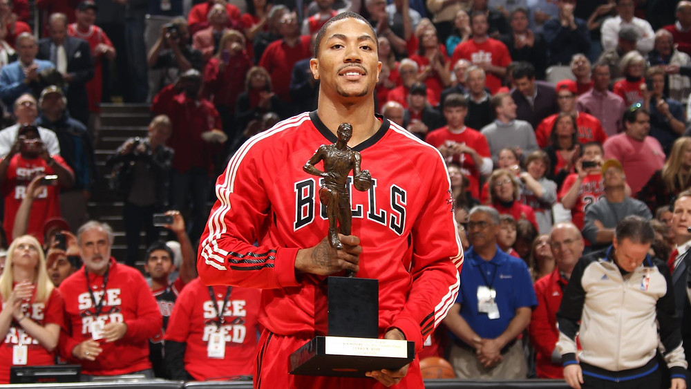 Point guard Derrick Rose of the Chicago Bulls holds his MVP trophy in 2011 before an NBA game.