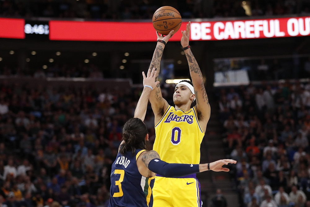 Kyle Kuzma of the Los Angeles Lakers shoots a 3-pointer over point guard Ricky Rubio during an NBA basketball game against the Utah Jazz.