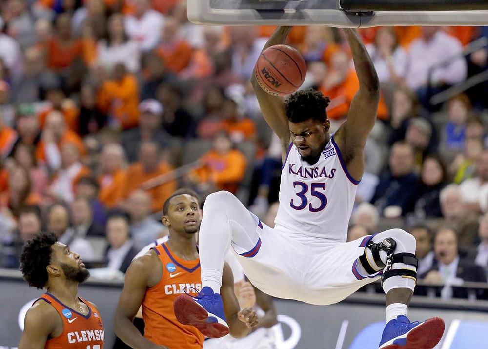 Kansas Jayhawks center Udoka Azubuike dunks ferociously against the Clemson Tigers in an NCAA basketball game.