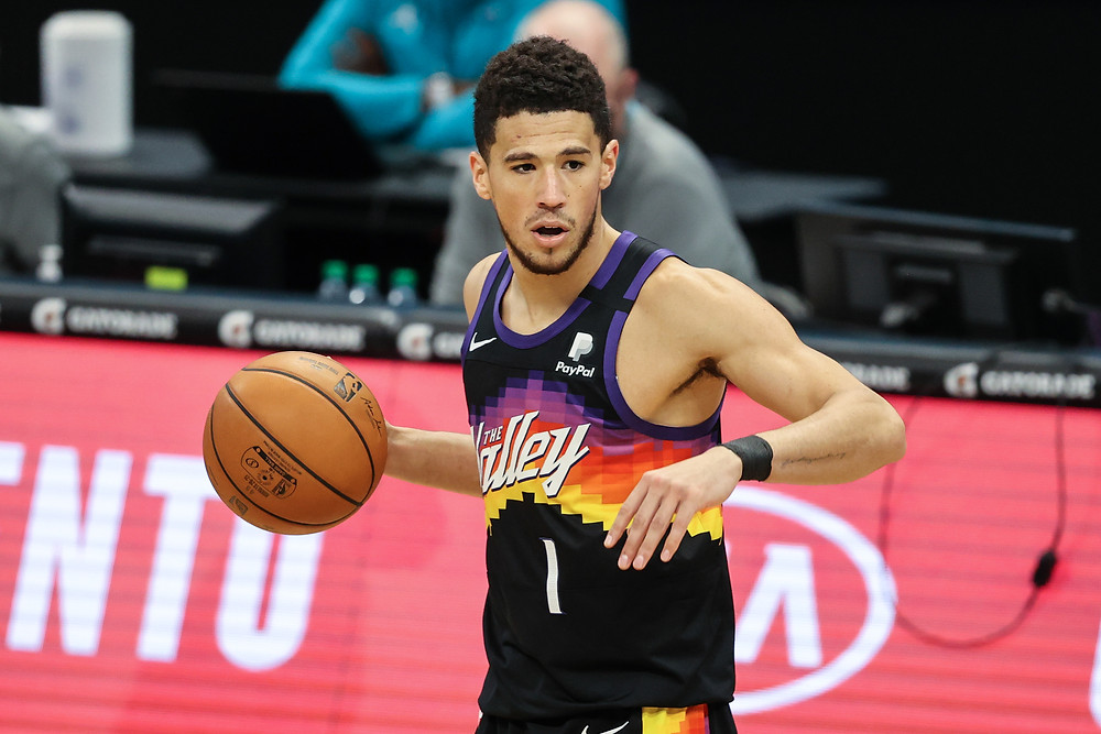 Phoenix Suns shooting guard Devin Booker relocates his teammate while dribbling during an NBA basketball game.