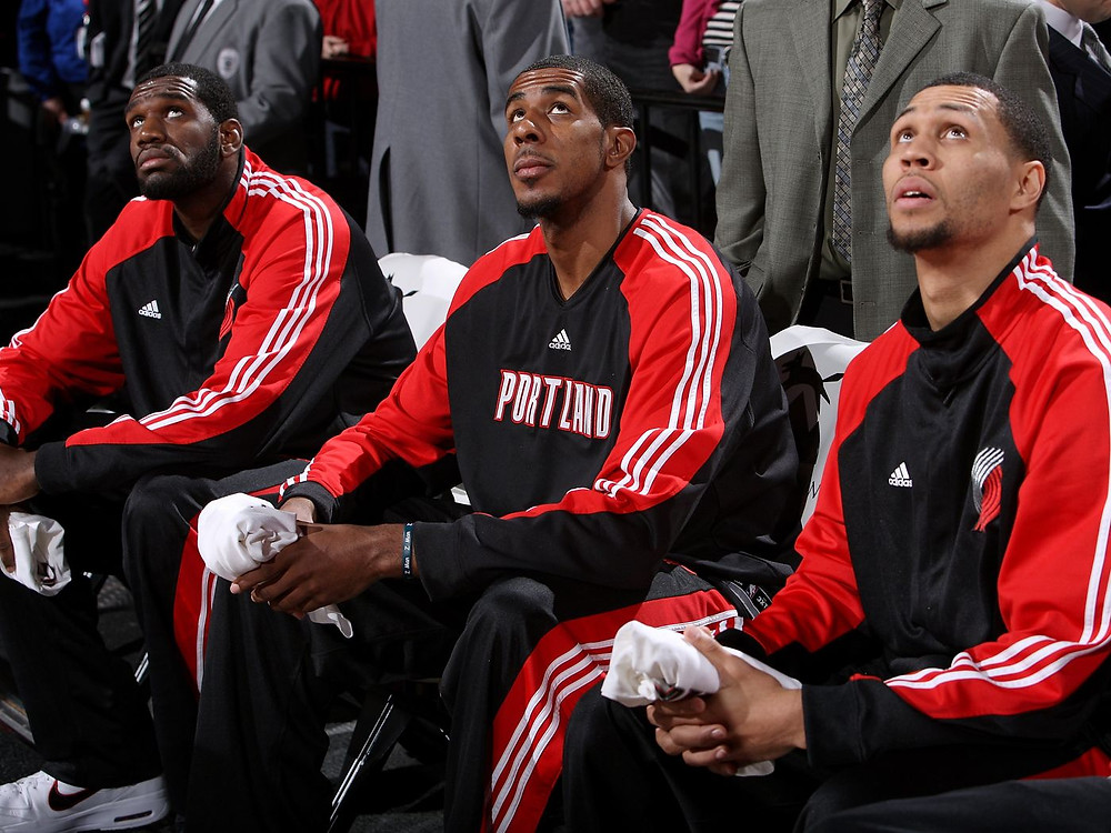 Greg Oden, LaMarcus Aldridge, and Brandon Roy of the Portland Trail Blazers look up at the arena jumbotron during an NBA basketball game.