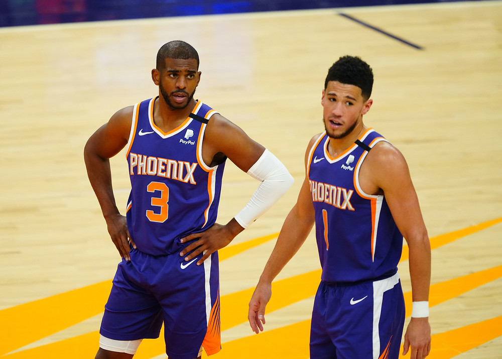 Chris Paul and Devin Booker of the Phoenix Suns discuss during an NBA basketball game.