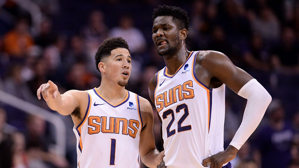 Devin Booker and Deandre Ayton of the Phoenix Suns discuss plays during an NBA basketball game.