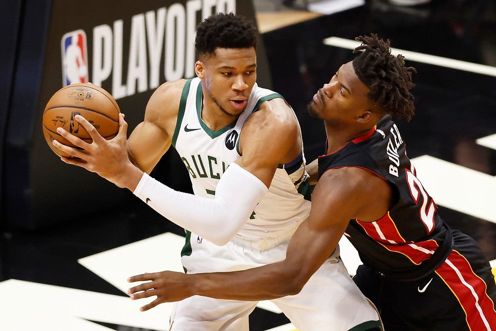Milwaukee Bucks forward Giannis Antetokounmpo posts up against a defending Jimmy Butler during their playoff matchup against the Miami Heat.