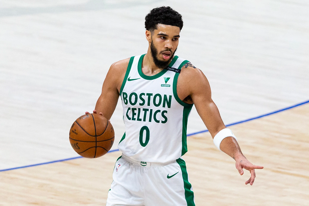 Boston Celtics small forward Jayson Tatum points toward the floor and directs his teammate during an NBA basketball game.
