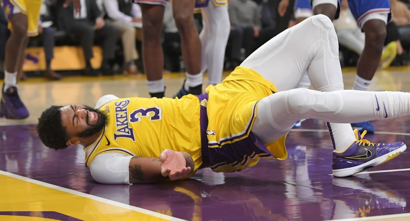 Los Angeles Lakers forward Anthony Davis clutches his back in pain following an injury during an NBA basketball game against the New York Knicks.