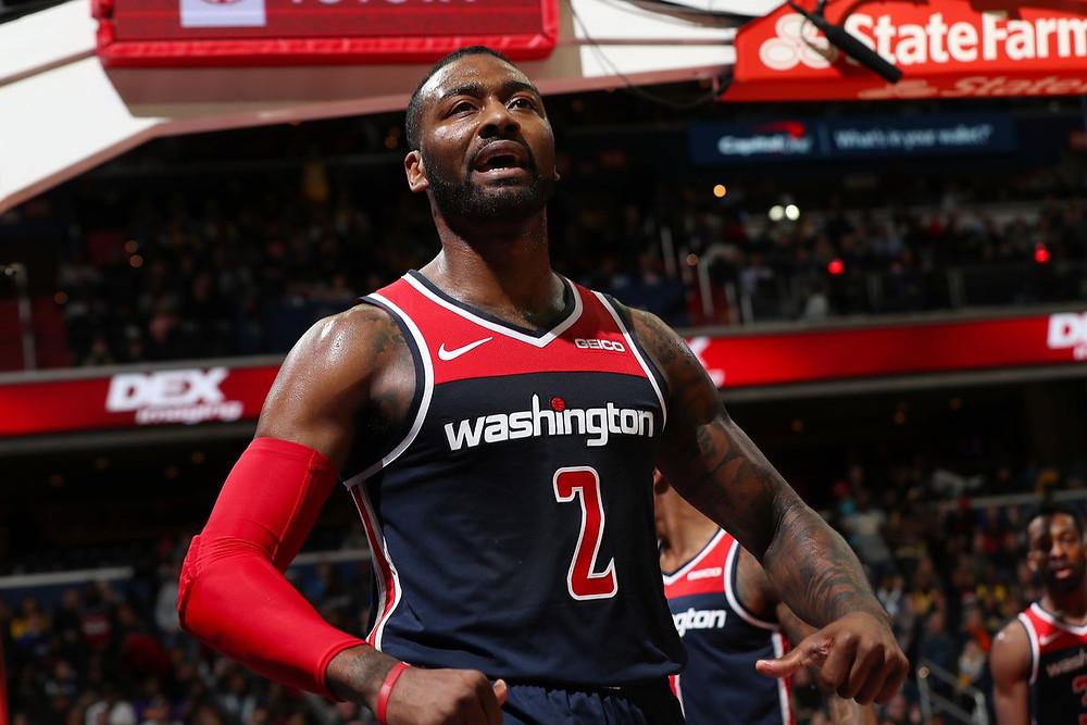 Former Washington Wizards point guard John Wall flexes after a made basket during an NBA basketball game.