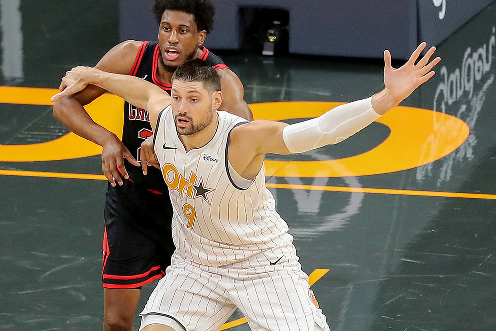 New Chicago Bull Nikola Vucevic calls for the ball while posting up against Thaddeus Young during an NBA basketball game.