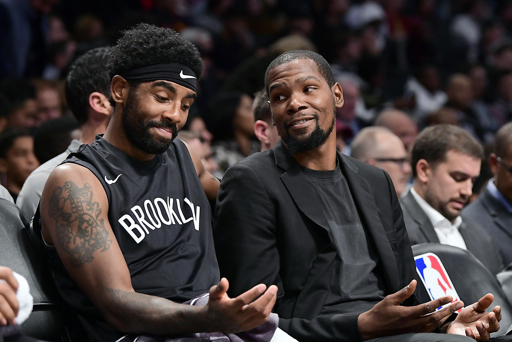 Kyrie Irving and Kevin Durant on the Brooklyn Nets talk on the bench during an NBA basketball game.