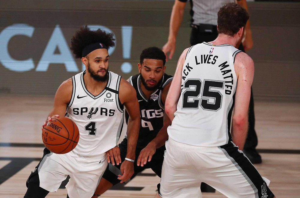 San Antonio Spurs guard Derrick White dribbles the ball around a screen set by teammate Jakob Poeltl in an NBA basketball game.