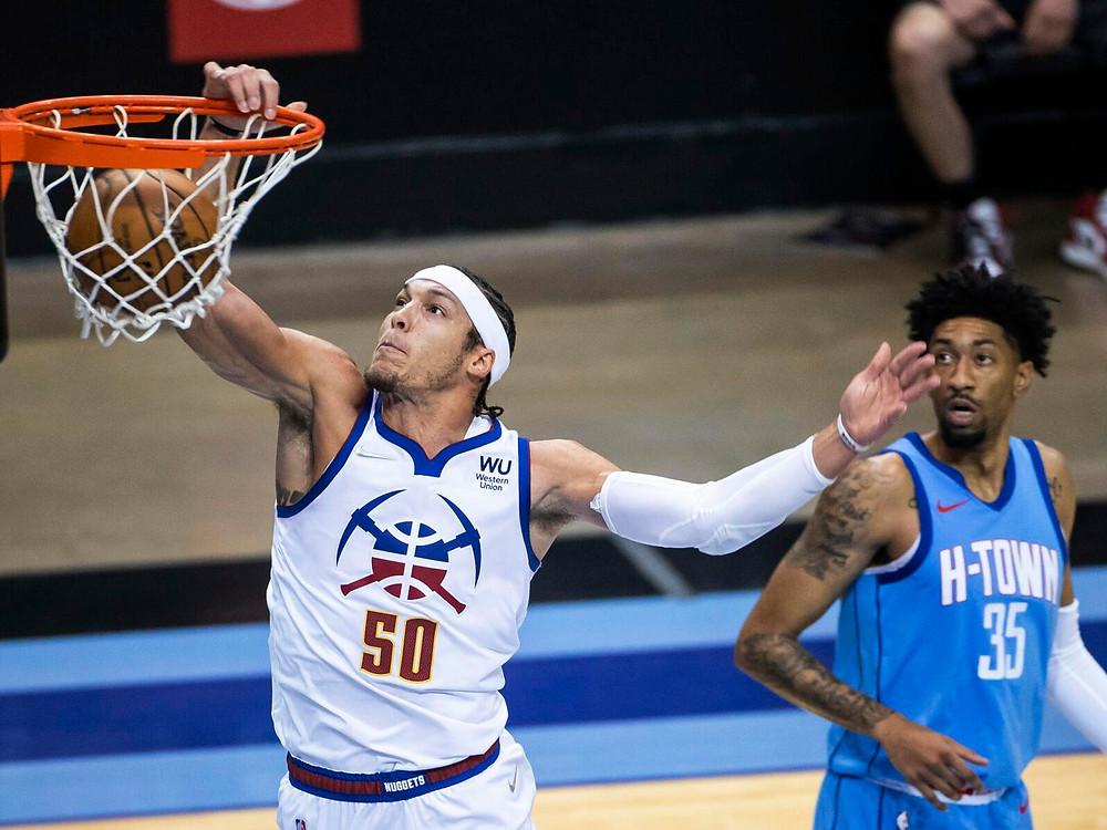 Denver Nuggets power forward Aaron Gordon dunks the basketball during an NBA basketball game against the Houston Rockets.