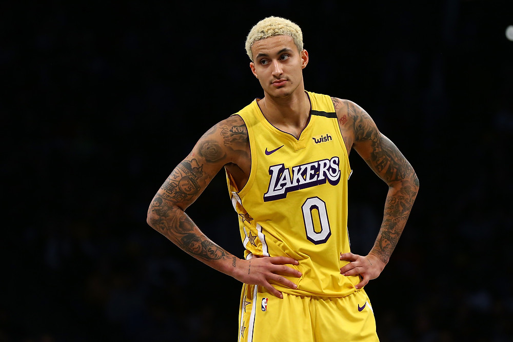 A bleach-blonde Kyle Kuzma of the Los Angeles Lakers rests his hands on his hips during an NBA basketball game.