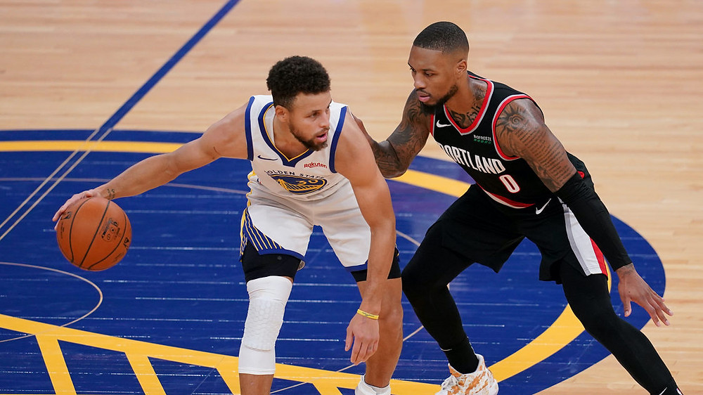 Golden State Warriors point guard Steph Curry dribbles the ball against Portland Trailblazers point guard Damian Lillard during an NBA basketball game on January 3rd, 2020 in Chase Center.