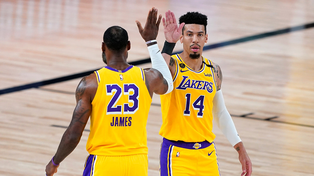 Los Angeles Lakers point guard LeBron James and shooting guard Danny Green high-five in the Orlando bubble during an NBA basketball game.