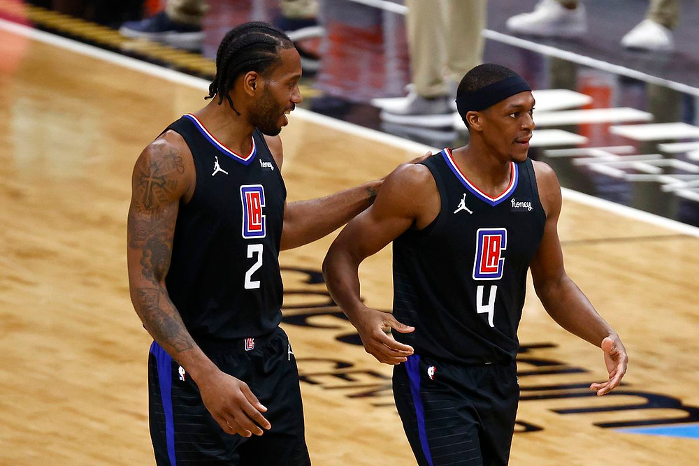 Kawhi Leonard and Rajon Rondo of the Los Angeles Clippers celebrate during a timeout in an NBA basketball game.
