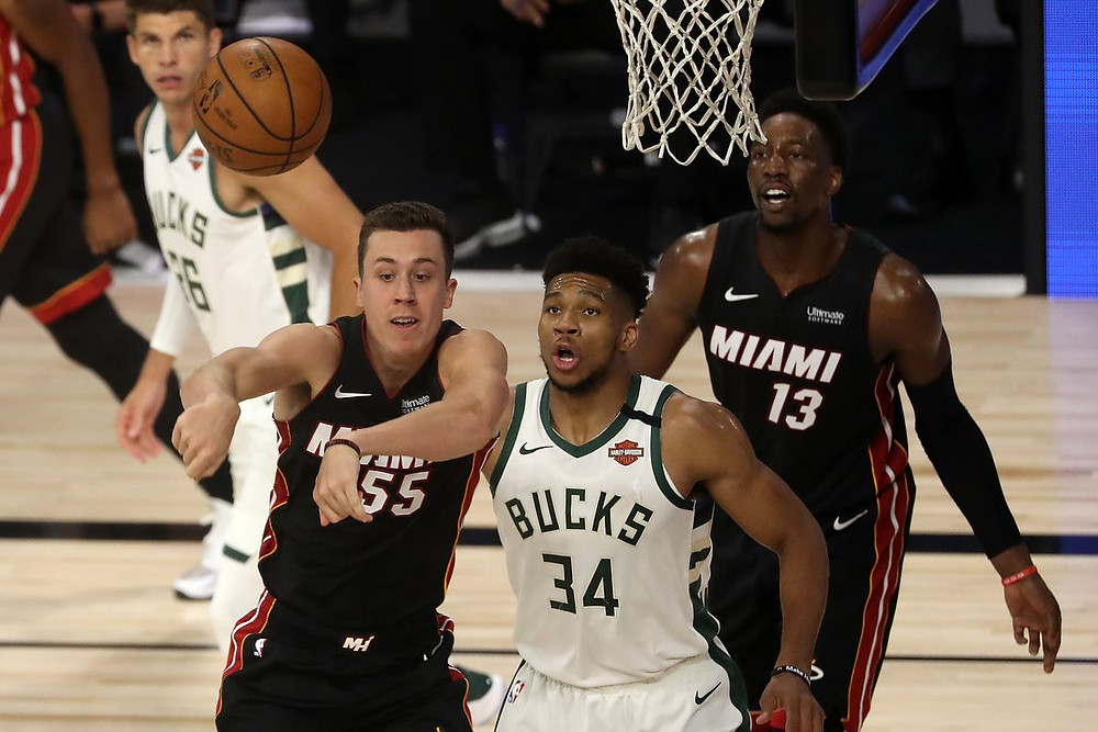 Kyle Korver of the Milwaukee Bucks watches as his teammate Giannis Antetokounmpo fights for position in the paint with Duncan Robinson and Bam Adebayo of the Miami Heat.