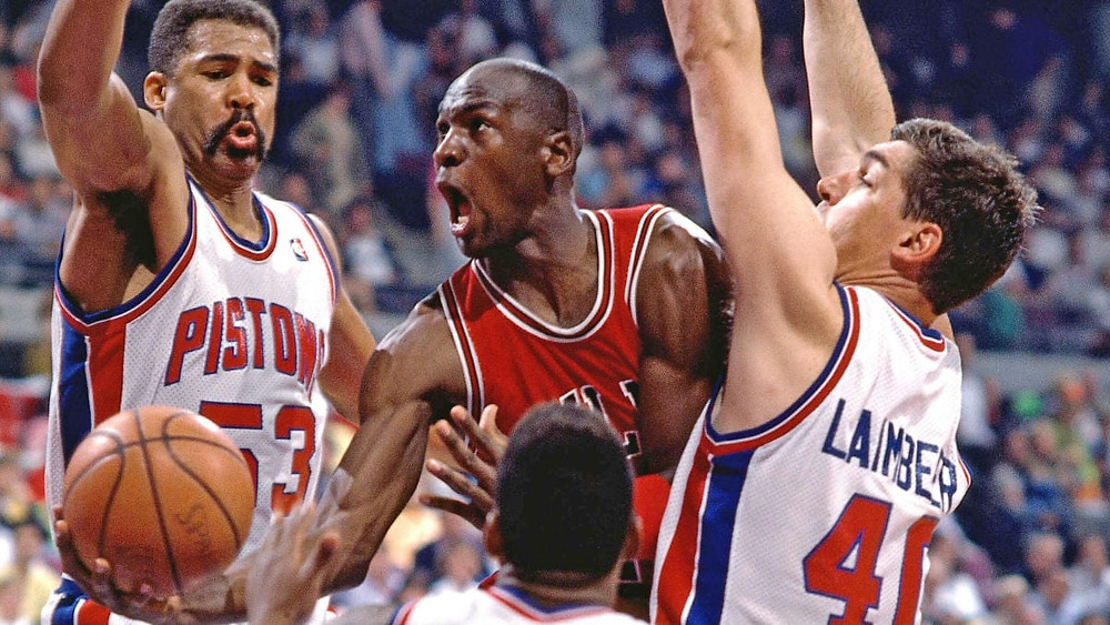 Chicago Bulls shooting guard Michael Jordan lays up the basketball while being defended by Detroit Pistons forwards James Edwards and Bill Laimbeer.