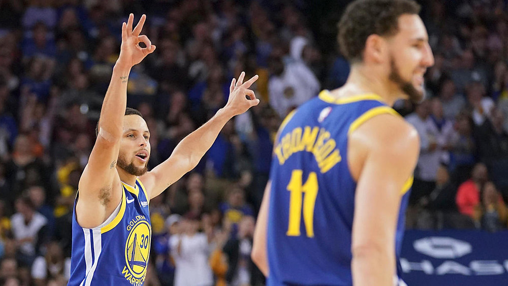 Golden State Warriors point guard Stephen Curry celebrates a made 3-pointer with shooting guard Klay Thompson in an NBA basketball game.