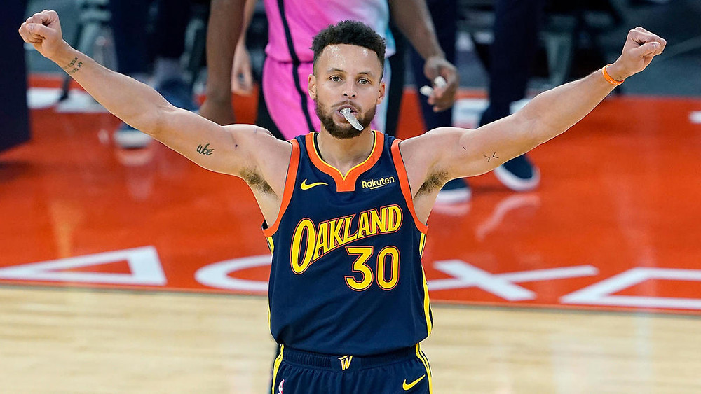 Golden State Warriors point guard Stephen Curry raises his arms in triumph during an NBA basketball game against the Miami Heat.