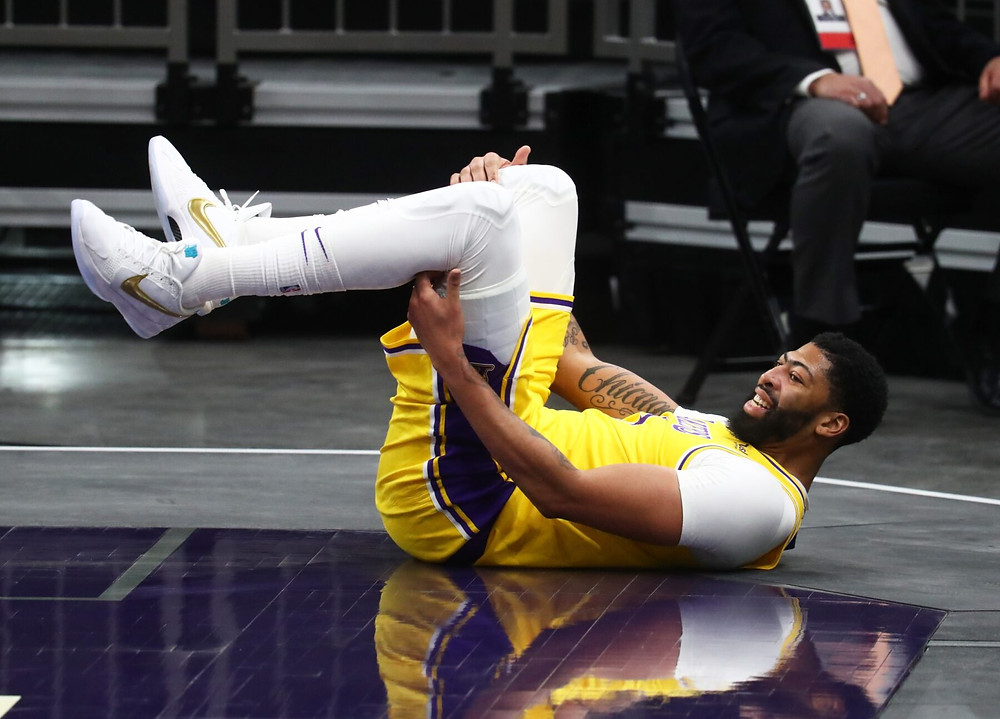 Los Angeles Lakers forward Anthony Davis grips his leg on the floor during an NBA basketball game on February 14.