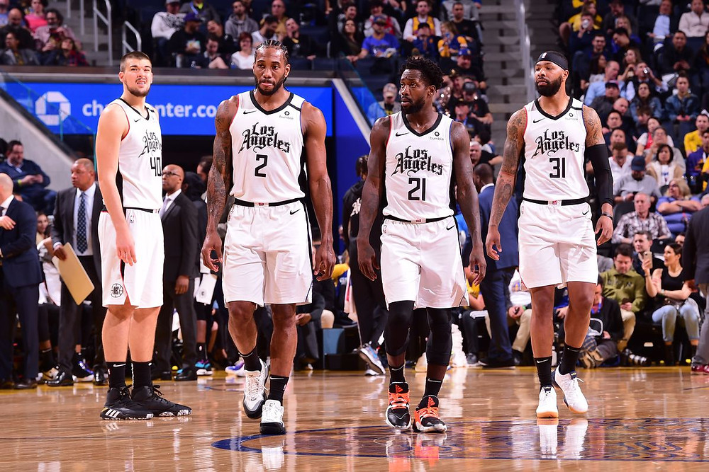 Ivica Zubac, Kawhi Leonard, Patrick Beverley, and Marcus Morris Sr. of the Los Angeles Clippers walk up the court in an NBA game.