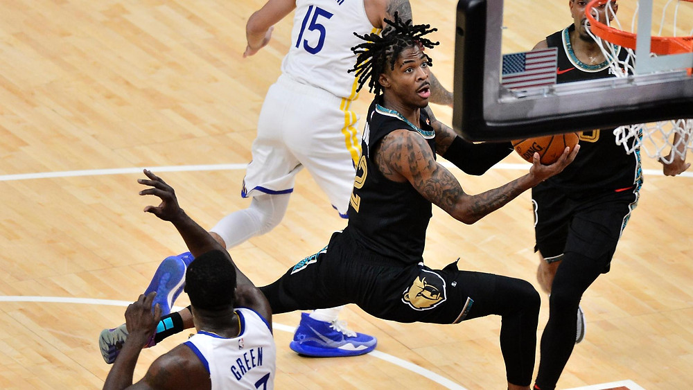 Memphis Grizzlies point guard Ja Morant hangs in midair for a layup attempt against the Golden State Warriors in an NBA basketball game.