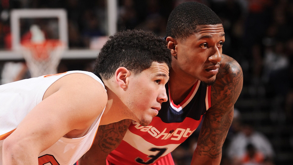 Phoenix Suns shooting guard Devin Booker and Washington Wizards shooting guard Bradley Beal face off in an NBA basketball game.