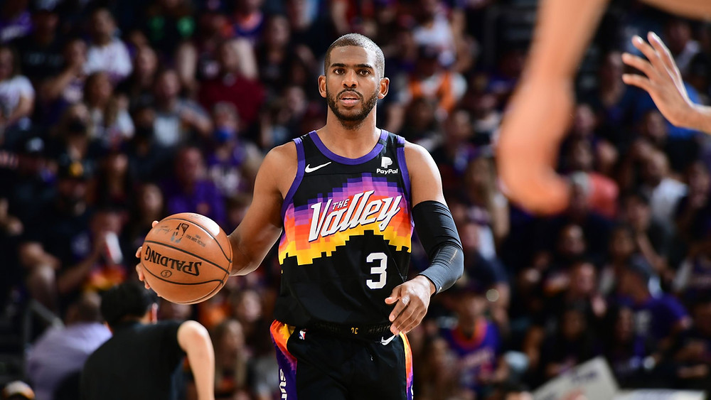 Phoenix Suns point guard Chris Paul dribbles the ball up the court during an NBA basketball game.