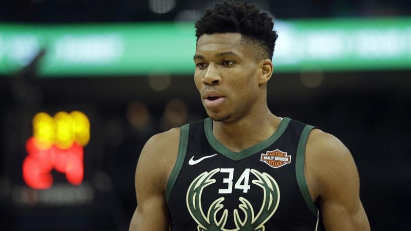 Giannis Antetokounmpo of the Milwaukee Bucks looks downwards as the basketball court during an NBA game.