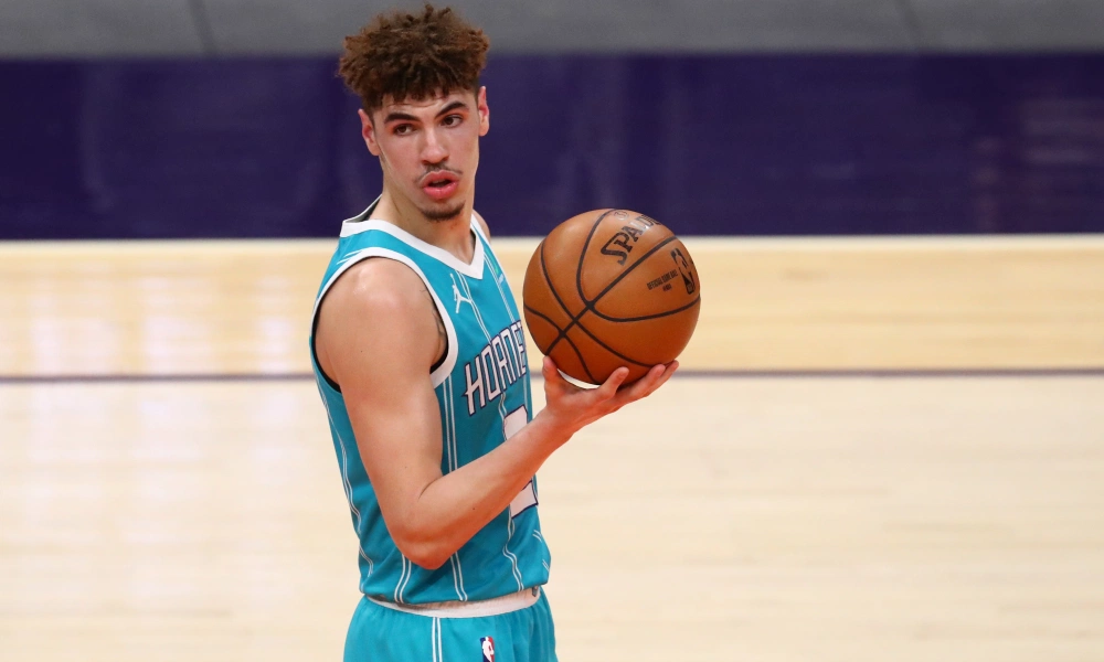 Charlotte Hornets point guard LaMelo Ball holds a basketball in his hand during an break in action during an NBA basketball game.