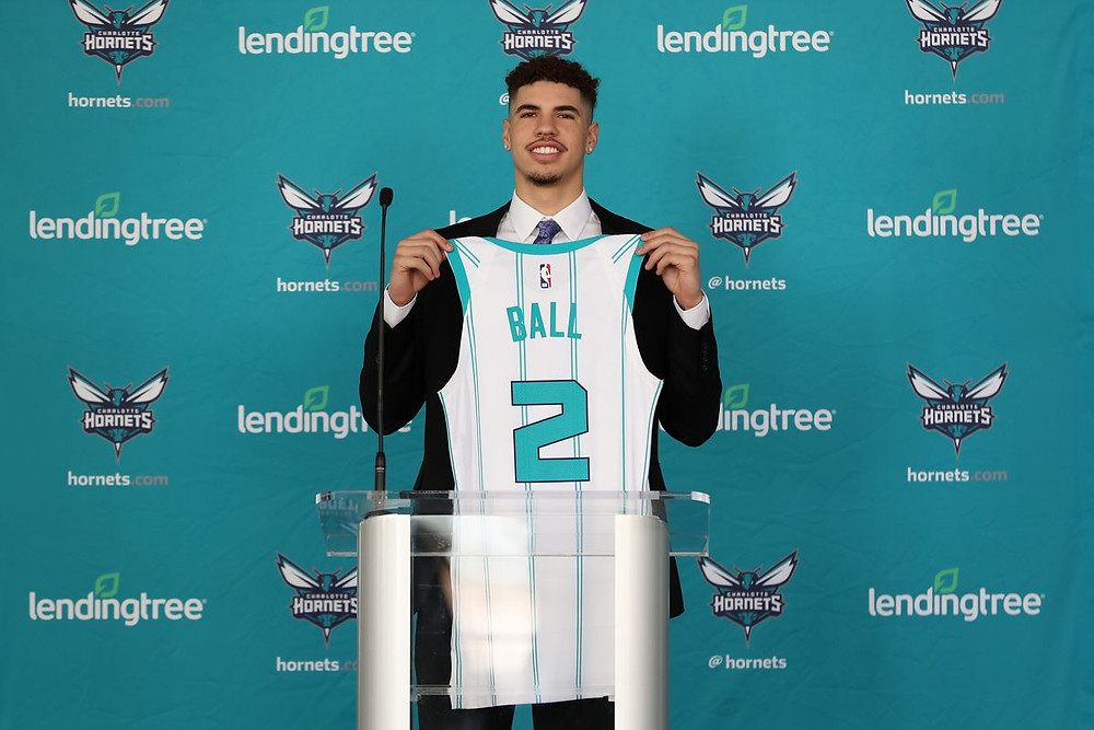 LaMelo Ball, drafted third overall in the 2020 NBA Draft, holds up his Charlotte Hornets jersey in his introductory press conference.