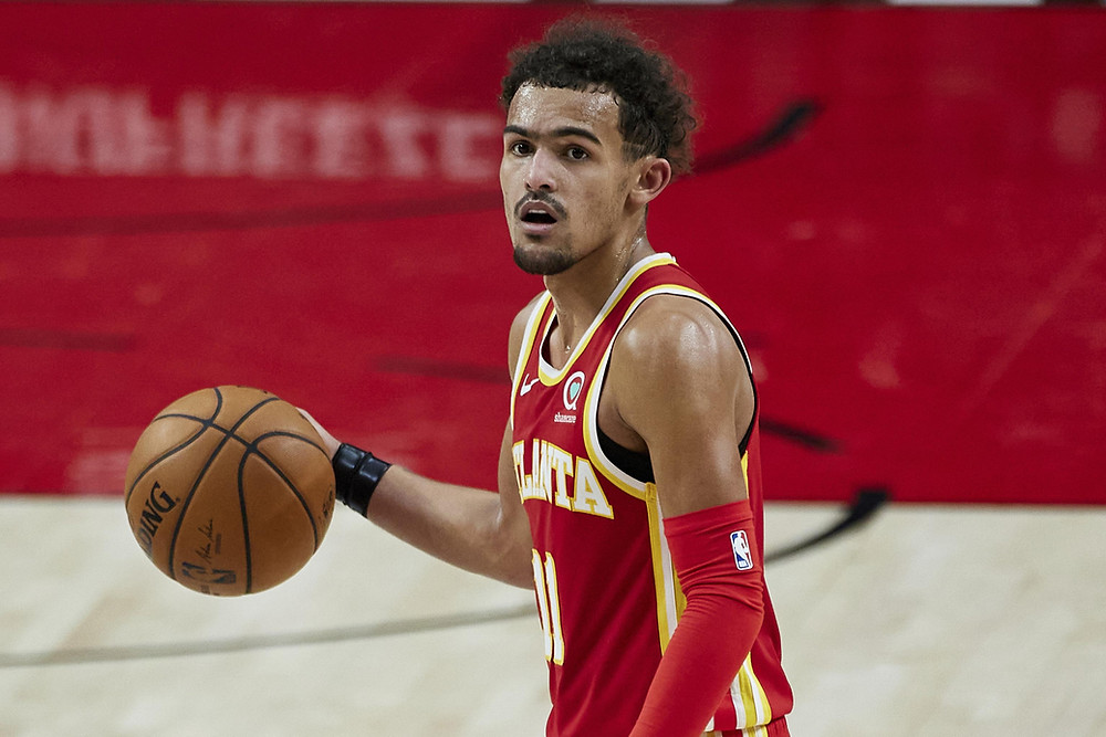 Atlanta Hawks point guard Trae Young dribbles the ball near the 3-point arc on offense during an NBA basketball game.